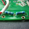 These two series-connected 5 megohm resistors form the top half of the voltage divider. Cold solder joint on the righmost lead.