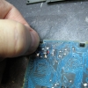 Press on one clip at a time with just enough pressure to slip the barb past the circuit board.