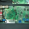 The main circuit board contains most of the analog circuitry. The voltage divider section is shielded with a metal can.  A trimmer capacitor for compensating the divider at higher frequencies can be seen near the shield.  There is a mix of SMD and through-hole components, typical of 1990s technology.